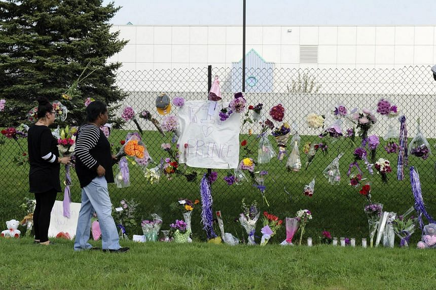 Fans and mourners place flowers on a fence outside of Paisley Park, the home and studio of singer Prince, in Minnesota, on April 21, 2016.