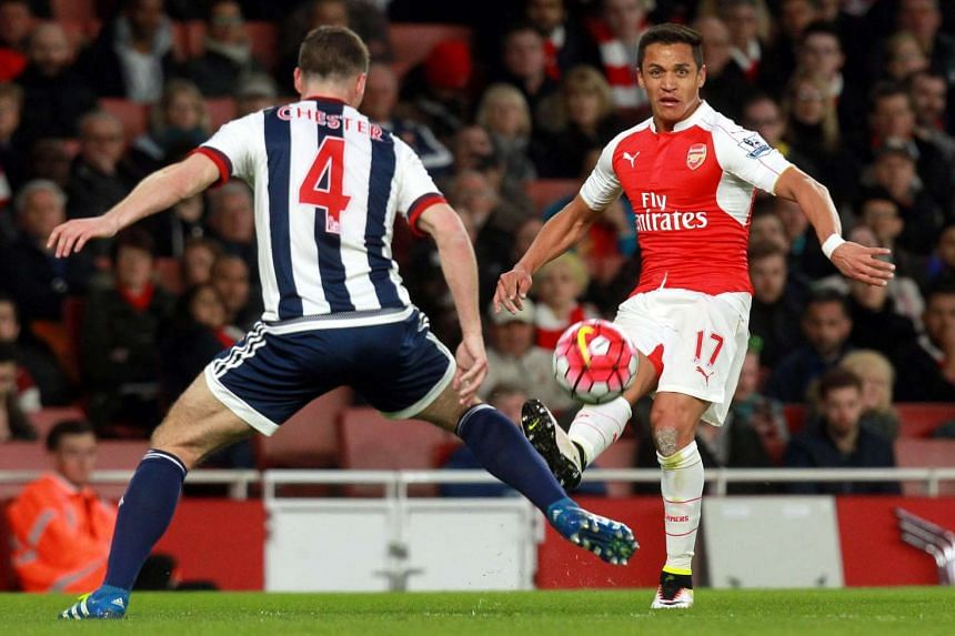 Arsenal's Alexis Sanchez (right) and West Bromwich's James Chester vie for the ball during Thursday's Premier League match at the Emirates Stadium in London.