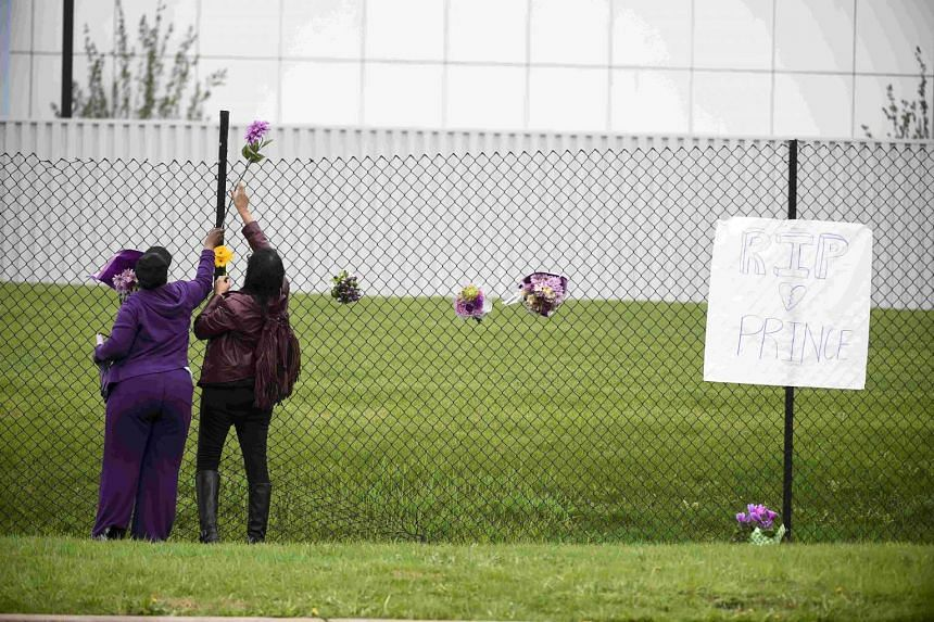 Prince fan, Mona Shelton, 42,  and an unidentified employee (left) place flowers on a fence at Prince's estate on Thursday.