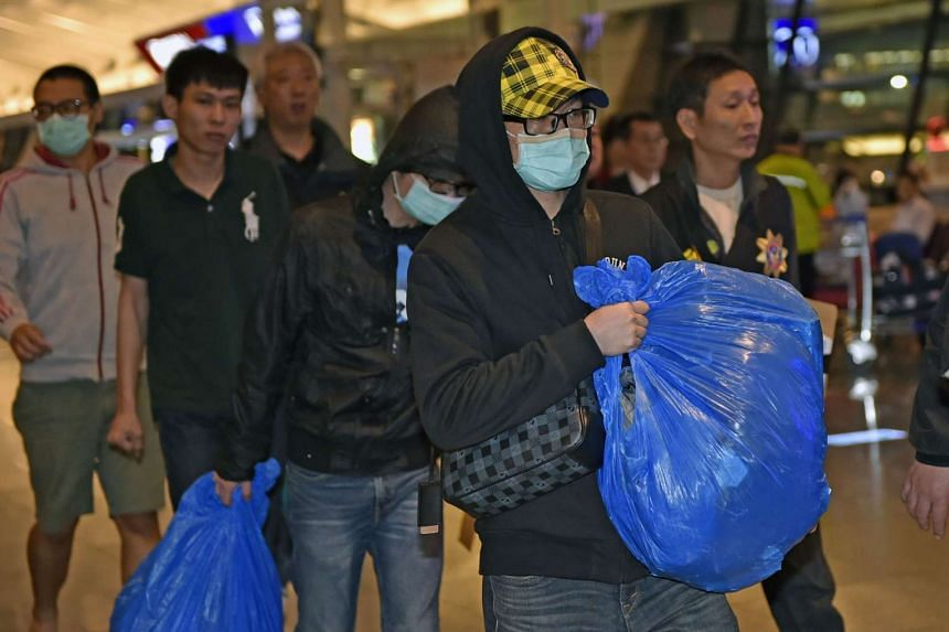 Masked alleged fraud suspects are escorted by policemen as they arrive at Taoyuan Airport in Taoyuan on April 15, 2016.