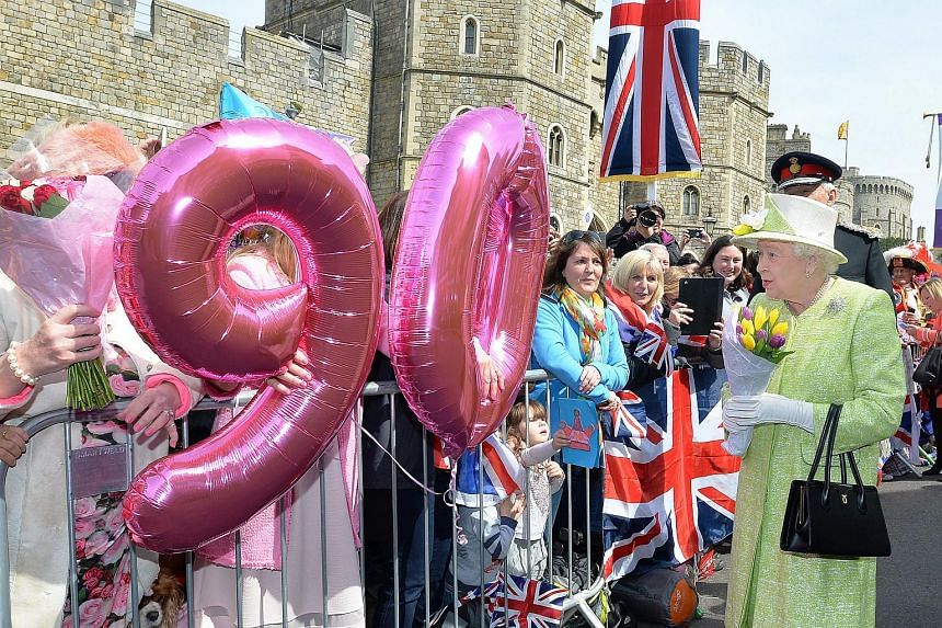 Britain's Queen Elizabeth II (right) greets well-wishers on her 90th birthday in Windsor, London, on April 21, 2016.