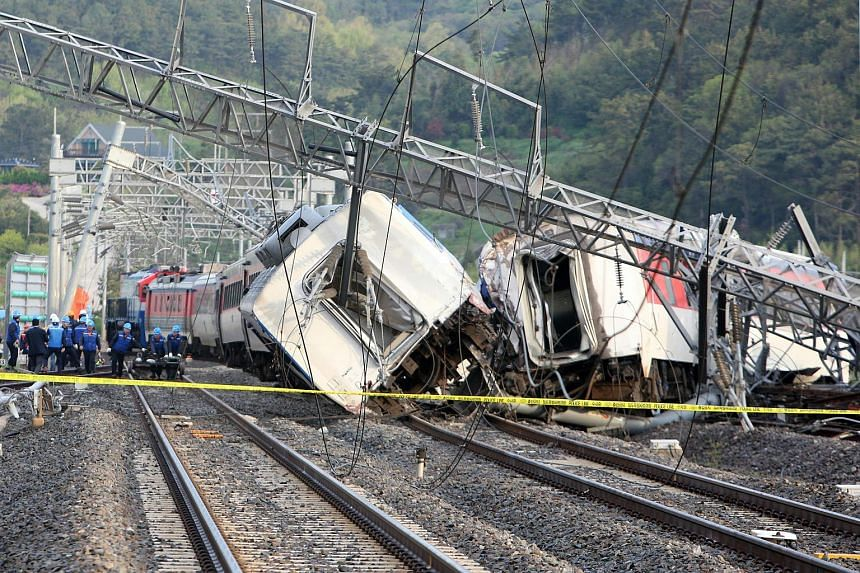 South Korean railway workers struggle to put a derailed passenger train back on track in the southern port city of Yeosu, on April 22, 2016.