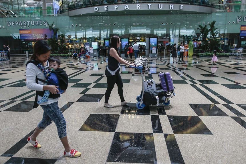 Travellers walk past an entrance to the transit area in the departure hall of the Changi Airport, Singapore, on April 19, 2016.