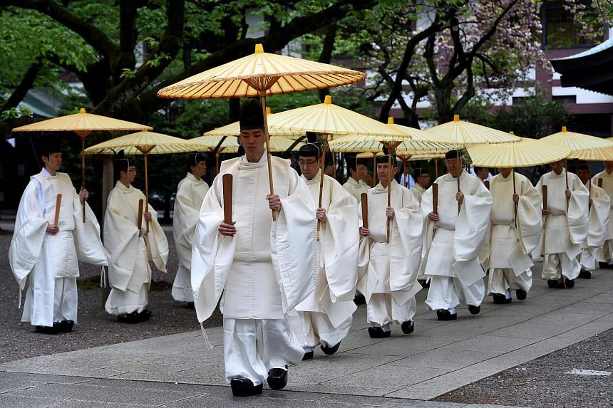 Shinto priests walk towards the outer shrine at the controversial Yasukuni shrine in Tokyo, on April 21, 2016.
