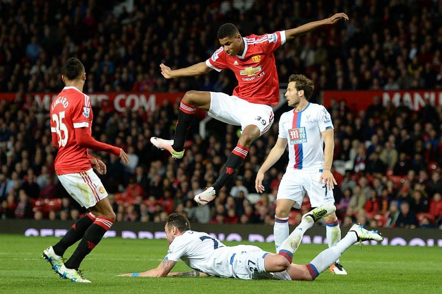Manchester United's striker Marcus Rashford (centre) jumps a tackle by Crystal Palace's defender Damien Delaney.