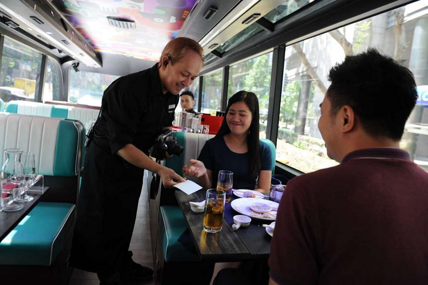 Singapore Gourmetbus host Glenford Kalaw, 45, serving passengers lunch on board the two-hour ride through the Civic District and Chinatown.