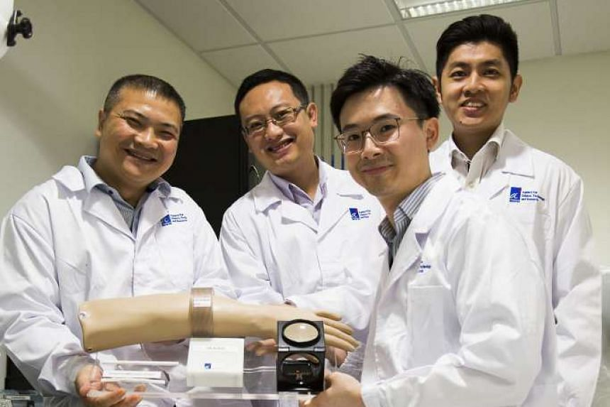 Members of the A*Star team (from left) Dr Alex Gu Yuandong, Dr Michael Ho Chee Keong, Dr Tan Ee Lim and Dr Cheong Jia Hao with the device they came up with in collaboration with vascular surgeon Benjamin Chua.