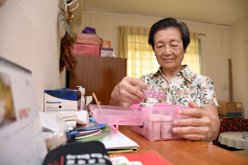 Madam Chan Soh Mui, 82, with a medicine box that has a sensor on its cover to detect when she opens it. Passive infra-red sensors were also installed on the walls to track her movements.