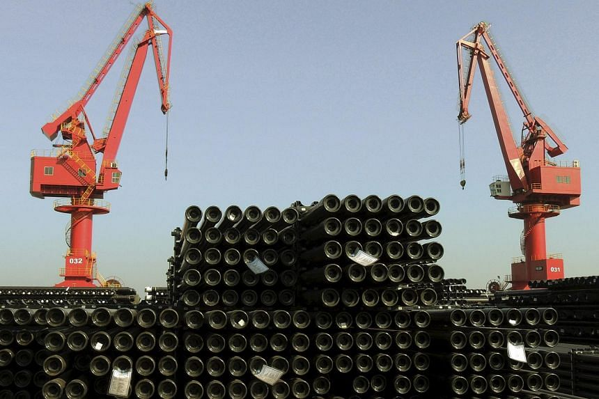 Cranes are seen above piles of steel pipes to be exported at a port in Lianyungang, Jiangsu province, China.