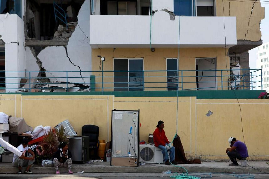 People sit outside a damaged building in Manta, Ecuador, on April 21, 2016.