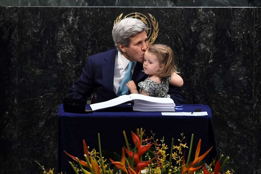 US Secretary of State John Kerry kisses his granddaughter, Isabelle Dobbs-Higginson, after signing during the signature ceremony for the Paris Agreement at the United Nations General Assembly Hall on April 22, 2016 in New York.