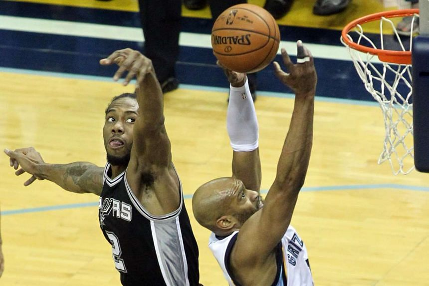 Memphis Grizzlies' Vince Carter (right) shoots as San Antonio Spurs' Kawhi Leonard defends in Game 3 of the first round of the NBA Playoffs.