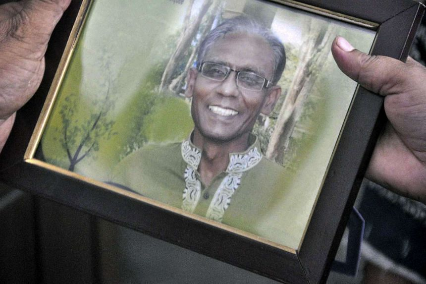 A man holds a portrait of Bangladeshi professor Rezaul Karim Siddique, who was hacked to death by unidentified attackers, on April 23, 2016.