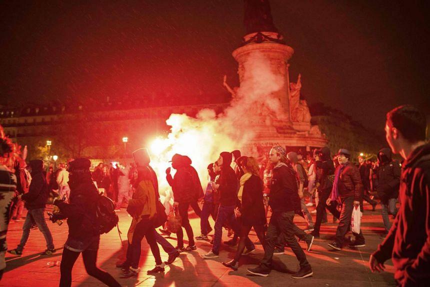 "Demonstrators hold flares at Place de la Republique during the ""Nuit Debout"" (Up All Night) movement in Paris, on April 22, 2016."