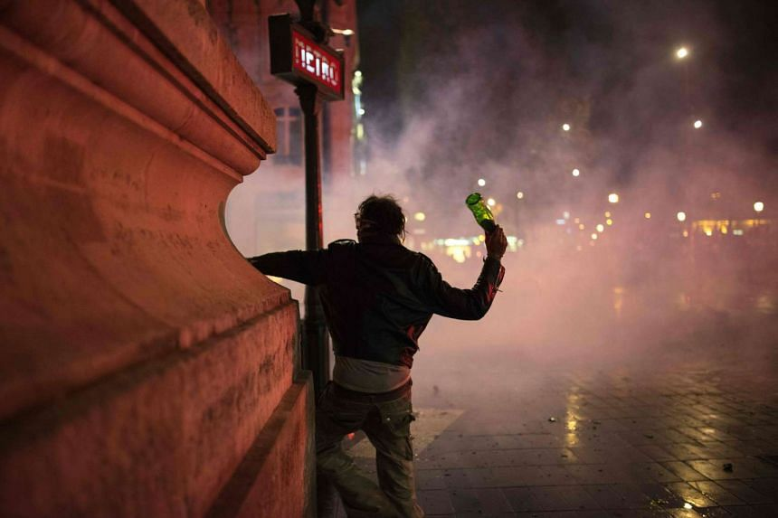 """A demonstrator throws a glass bottle to riot policemen during a protest following the """"Nuit Debout"""" (Up All Night) movement in Paris, on April 22, 2016."""
