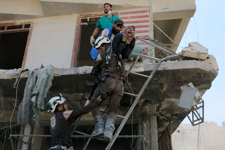 Syrian civil defence volunteers evacuate people from a damaged building following an airstrike on April 23, 2016, in Aleppo.