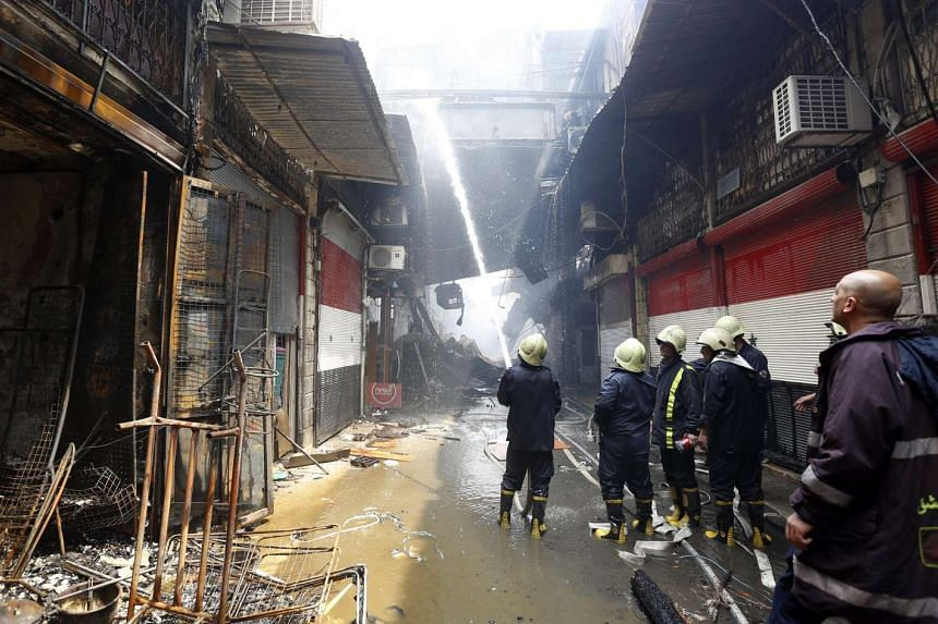 Firefighters spray water on burned shops at al-Asroneiyeh area in the old city of Damascus, Syria, on April 23, 2016.