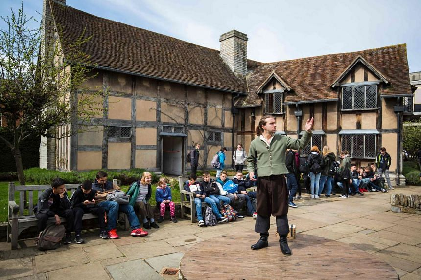 Actor Louis Osborne performs a soliloquy from the play 'Hamlet' outside the house where William Shakespeare was thought to be born, in Stratford-upon-Avon, on April 12, 2016.