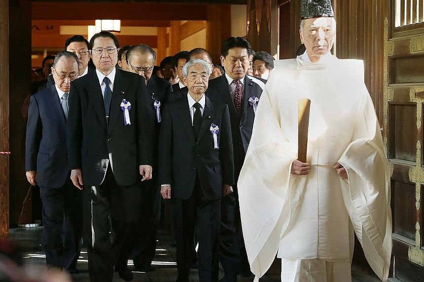 A Shinto priest leading lawmakers to the altar of Yasukuni Shrine in Tokyo yesterday.