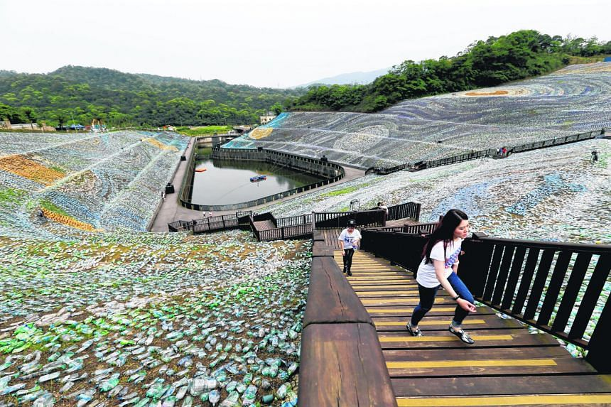 """Visitors walking around """"The Starry Paradise"""", a re-creation of Vincent Van Gogh's painting The Starry Night (left) made from plastic bottles at the Embrace Cultural and Creative Park at Keelung in northern Taiwan. About four million discarded plasti"""