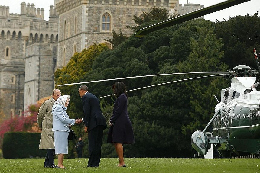 Mr Obama and First Lady Michelle Obama greeting British Queen Elizabeth II and Prince Philip after landing by helicopter at Windsor Castle for a private lunch yesterday.