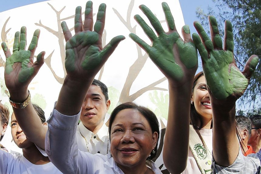 Filipino senator Cynthia Villar (centre) participating in a hand-painting exercise with environmental advocates on the coast of Freedom Island to mark Earth Day in Las Pinas City, south of Manila, yesterday. Earth Day is celebrated annually on April