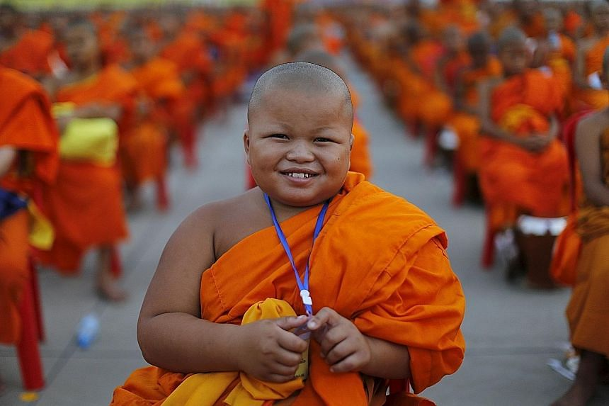 A novice posing for a picture yesterday while monks gathered to receive alms at Wat Phra Dhammakaya temple, in what organisers said was a meeting of 100,000 monks in Pathum Thani, outside Bangkok.