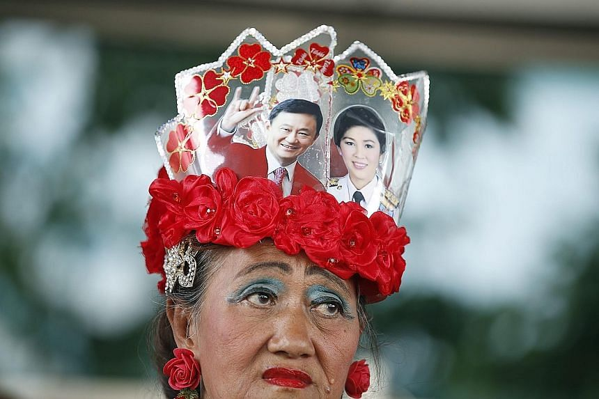Photos of former premiers Thaksin and Yingluck Shinawatra adorn the hat of a supporter outside a Bangkok court where Ms Yingluck appeared yesterday.