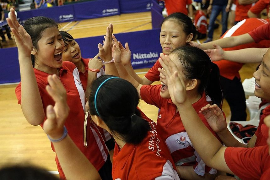 Above: SSP paddlers (from left) Wong Xin Ru and Lew Yen Lin celebrating with team-mates after winning the crucial fourth match in the B girls' final. Left: An elated Ryan Goh feeling on top of the world after RI won the A boys' final but he later ear