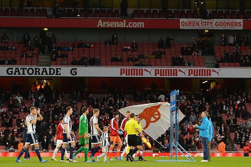 Empty seats are visible at the Emirates Stadium as the players come on to the pitch during the Premier League match between Arsenal and West Bromwich Albion on Thursday. There is a growing disenchantment among Arsenal supporters about the team's disa