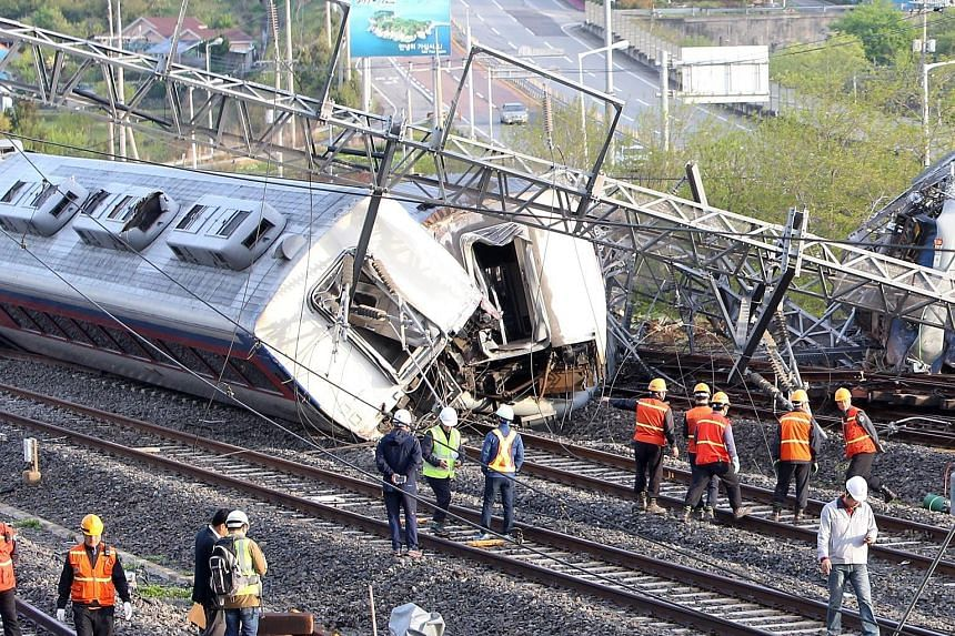 Rescue workers at the site where a train derailed in Yeosu, South Korea, yesterday. The overnight train, which left Seoul late on Thursday, derailed at 3.40am, killing an engineer and injuring eight others, railway operator Korail said. The accident