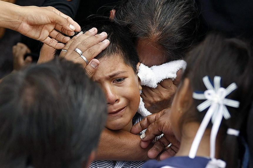 A woman trying to console an eight-year-old boy whose mother died in the April 16 earthquake, during her funeral in Manta, Ecuador, on Thursday.