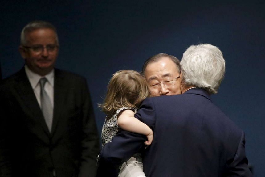 UN Secretary General Ban Ki-moon embracing US Secretary of State John Kerry who is holding his two-year-old granddaughter Isabelle Dobbs-Higginson, after signing the Paris Agreement on climate change at United Nations Headquarters in New York, US, on