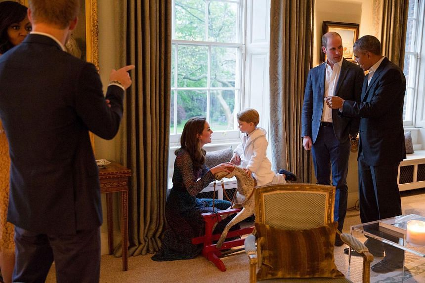 A handout picture released by Kensington Palace showing Britain's Prince George of Cambridge (right) playing on a rocking horse with his mother Catherine, Duchess of Cambridge, as US President Barack Obama (right) and Prince William, Duke of Cambridg
