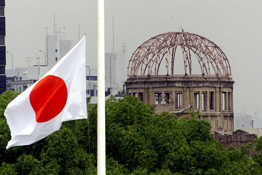 The Japanese national flag fluttering at half-mast in the foreground of the atomic bomb dome at the Hiroshima Peace Memorial Park, in western Japan on Aug 6, 1998.