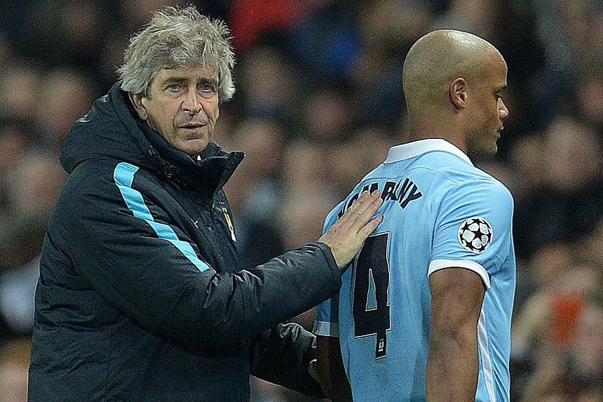 Manchester City's Chilean manager Manuel Pellegrini (left) consoling defender Vincent Kompany as he leaves the pitch injured during a Uefa Champions League last 16, second leg football match in Manchester, north west England, on March 15, 2016.