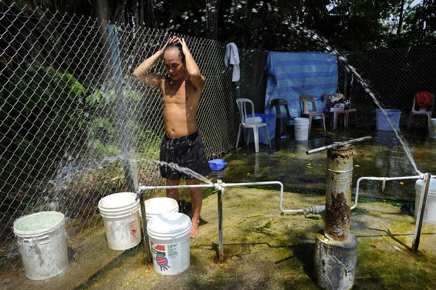 Mr Charlie Wong rinsing himself at the Sembawang Hot Spring to keep cool in the heat in 2012.