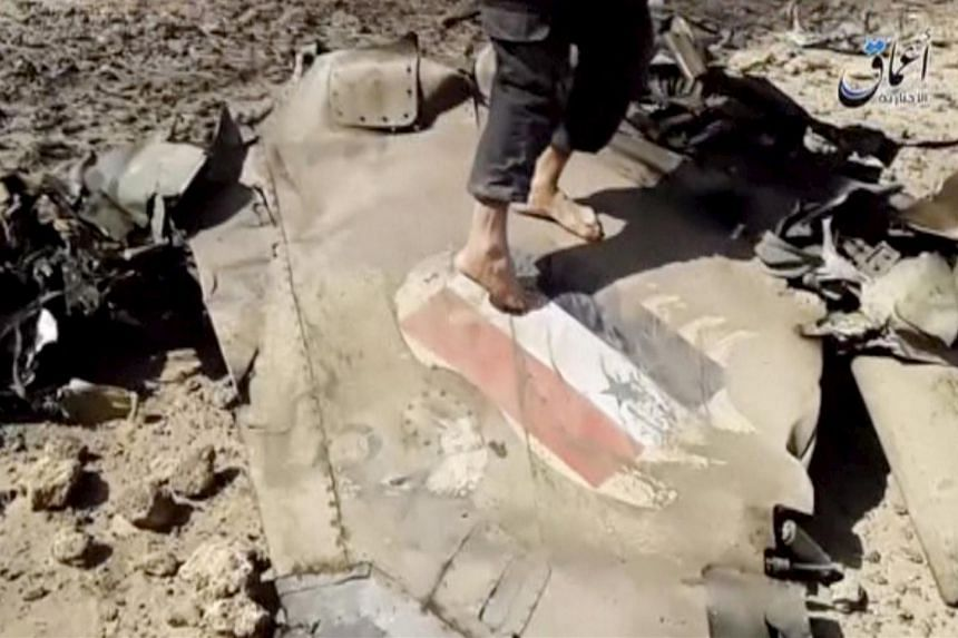 A man walking on the wreckage of a plane that crashed east of Damascus, in this still image taken from video said to be shot on April 22.