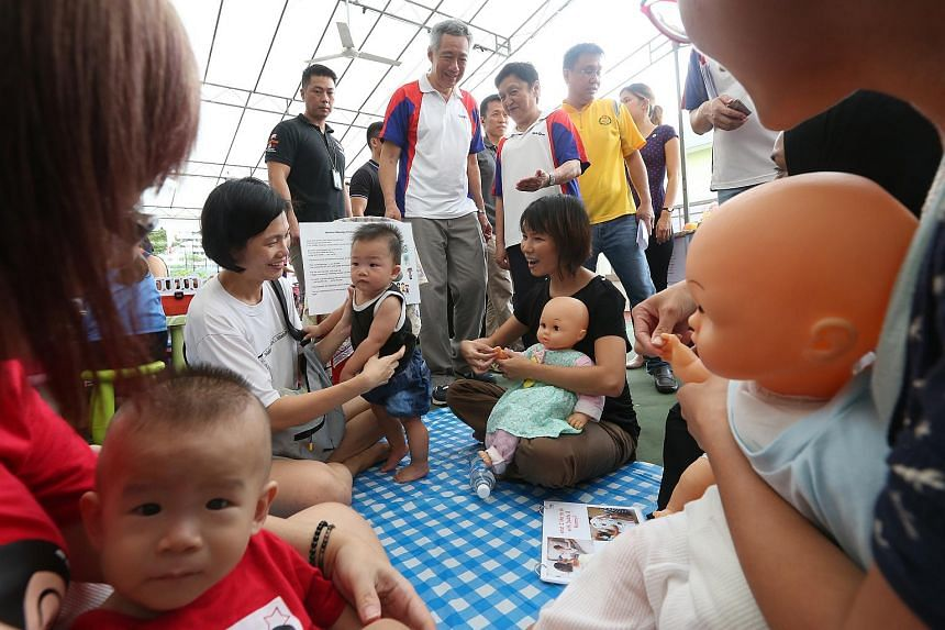 Prime Minister Lee Hsien Loong tours one of the carnival booths where mothers learn about baby massaging at the Teck Ghee healthy baby contest held at Teck Ghee Community Centre on April 24, 2016.