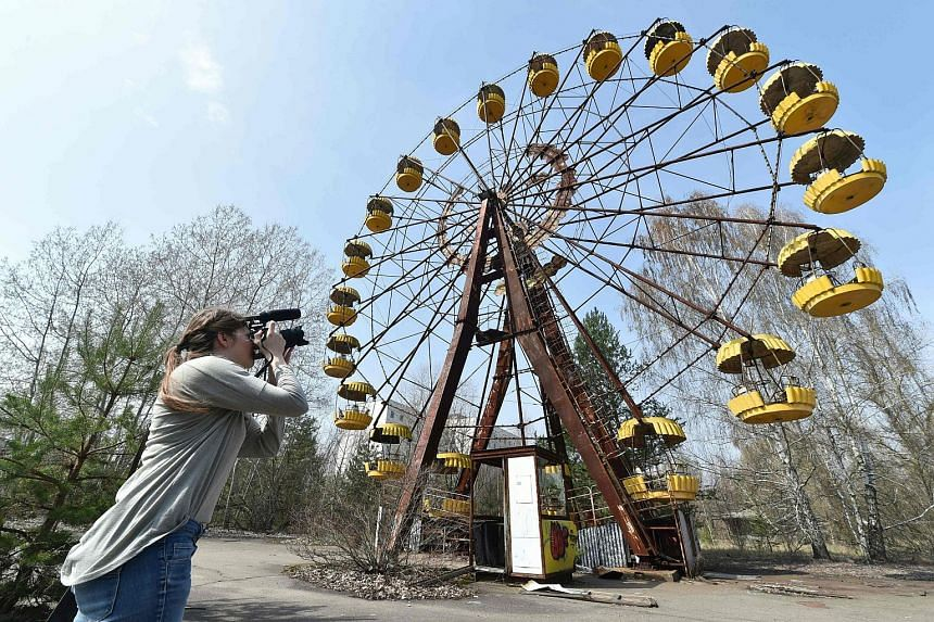 A woman films a Ferris wheel in the ghost city of Prypyat near Chernobyl Nuclear Power Plant on April 8, 2016.