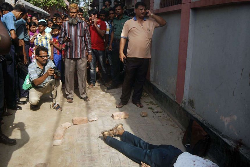 People gather around the body of Bangladeshi professor Rezaul Karim Siddique after he was hacked to death by unidentified attackers in Rajshahi on April 23, 2016.