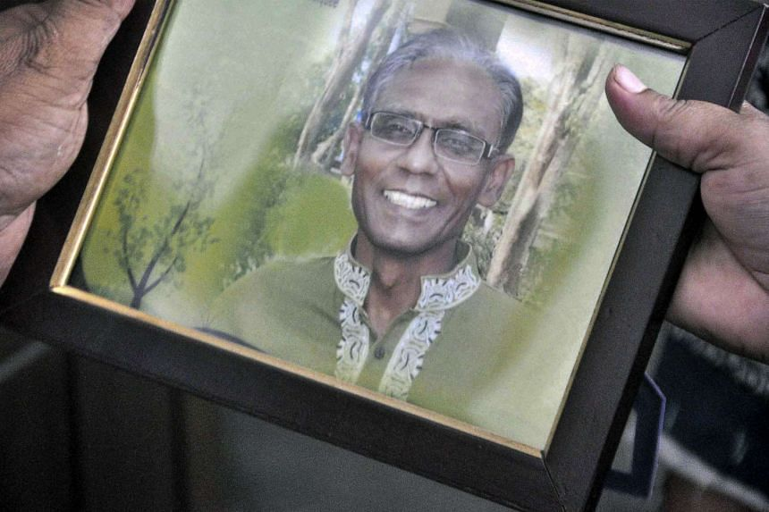A man holds a portrait of Bangladeshi professor Rezaul Karim Siddique, who was hacked to death by unidentified attackers, in Rajshahi on April 23, 2016.
