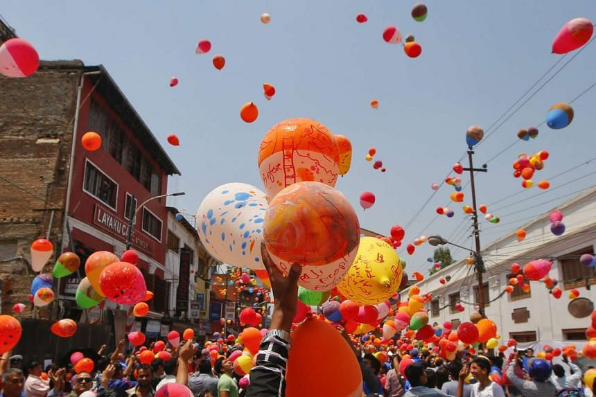 Nepalese people gather to release balloons at Kathmandu Durbar Square in memory of people who died in the earthquake a year ago, in Kathmandu, Nepal on April 23, 2016.