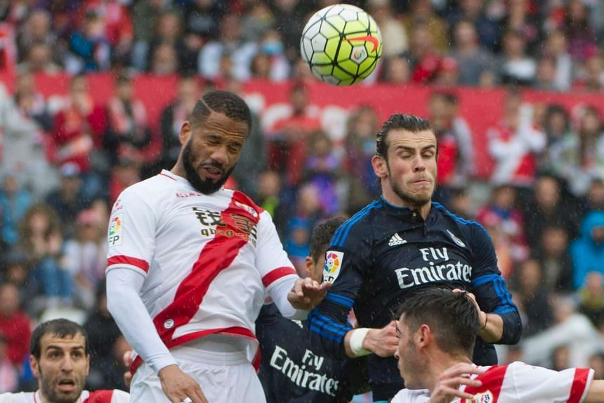Real Madrid's Welsh forward Gareth Bale (right) heads the ball with Rayo Vallecano's Portuguese forward Tiago Correia during the Spanish league football match Rayo Vallecano de Madrid vs Real Madrid CF at the Vallecas stadium in Madrid on April 23, 2