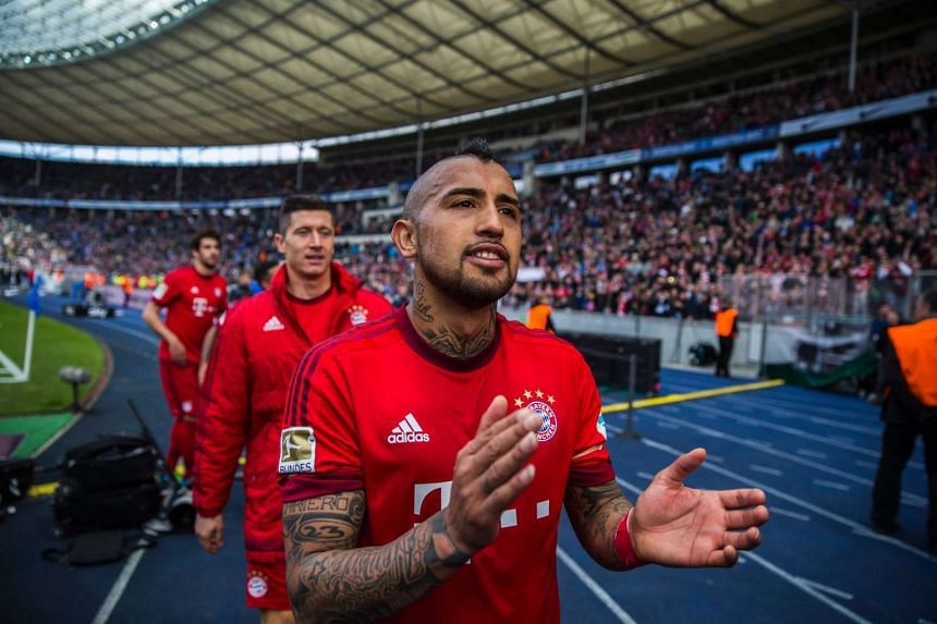 Bayern Munich's Chilean midfielder Arturo Vidal and team mates celebrate with fans after a 2-0 win in the German first division Bundesliga football match Hertha Berlin vs Bayern Munich at the Olympic stadium in Berlin on April 23, 2016.