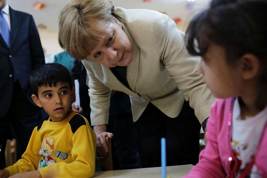 German Chancellor Angela Merkel talks with refugee children at a preschool, during a visit to a refugee camp on April 23, 2016 on the Turkish-Syrian border in Gaziantep.