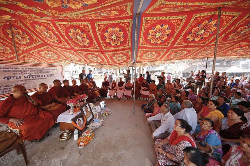 Nepalese Buddhist monks lead a prayer meeting attended by family members of earthquake victims at the remains of the Kasthamandap Temple in Kathmandu, Nepal on April 24, 2016.