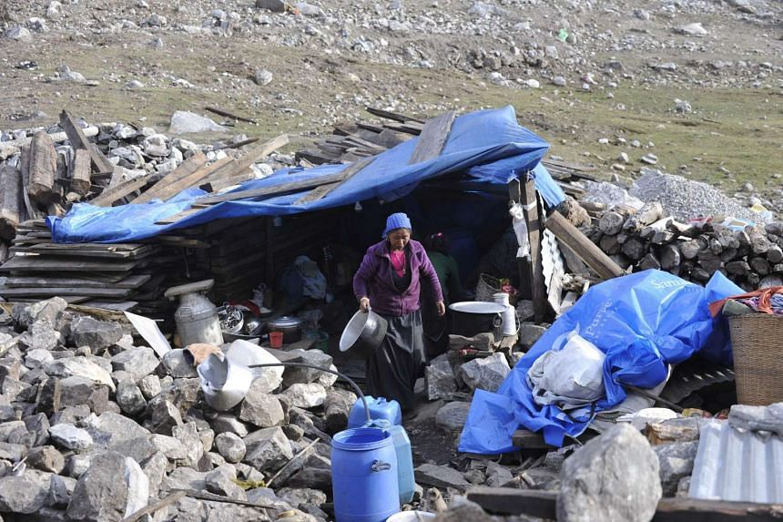 Nepalese villagers prepare to cook food in a temporary shelter in the village of Langtang on April 7, 2016.