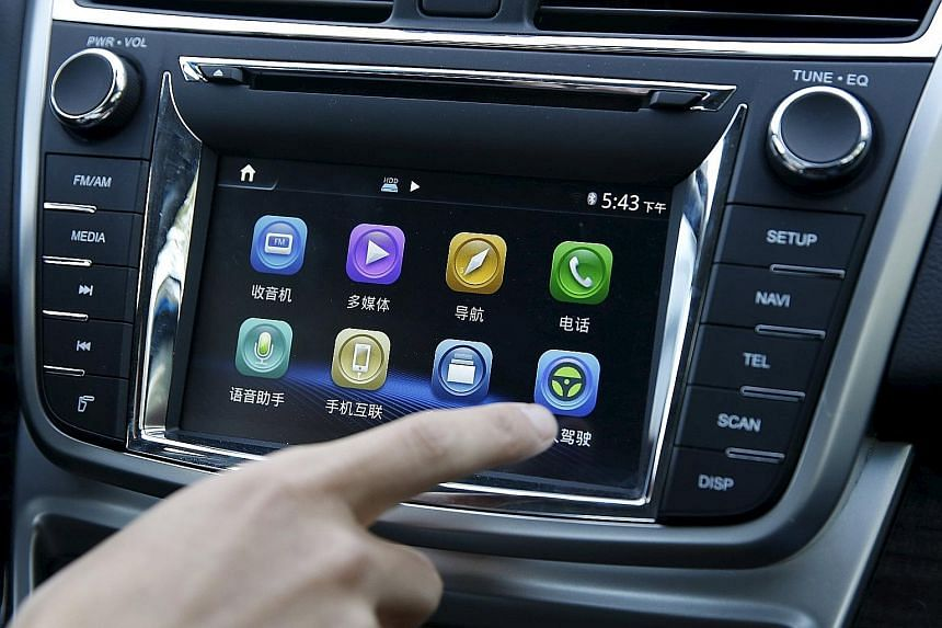 An engineer activates a button for the self-driving mode of Changan Automobile's self-driving car, a modified Raeton sedan, during a test drive in Beijing. China could unveil as early as this year a draft road map for having highway-ready, self-drivi