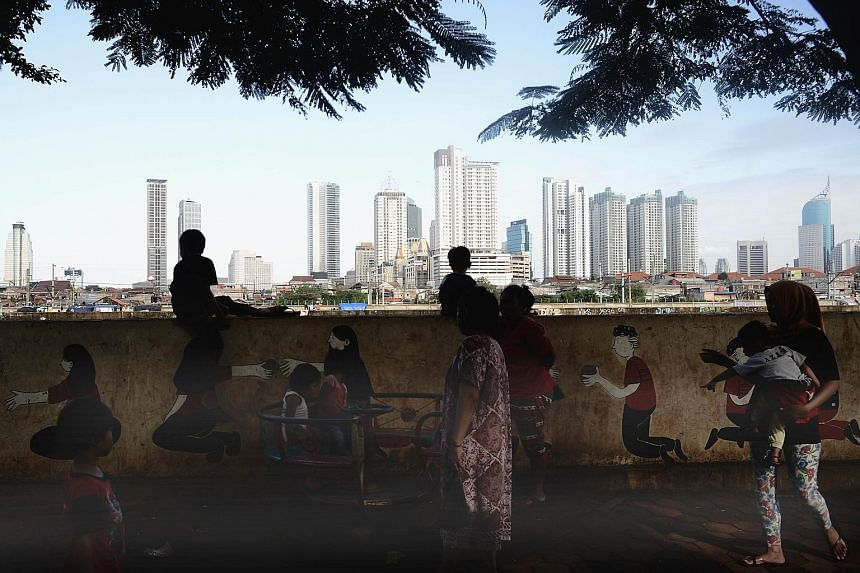 Indonesian children playing by a riverbank opposite the city centre in Jakarta. If Indonesia is to promote new industries, it must act fast. The country's working age population is expected to peak between 2025 and 2030, and economists say it must ta